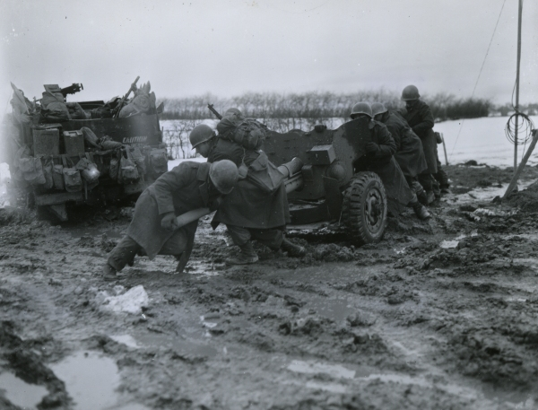 The Blue Spaders manhandle one of their 57mm anti-tank guns into position prior to the German onslaught. December 17, 1944.