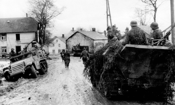 Waffen SS panzergrenadiers move past wrecked American equipment during the 1st days of the Ardennes offensive.