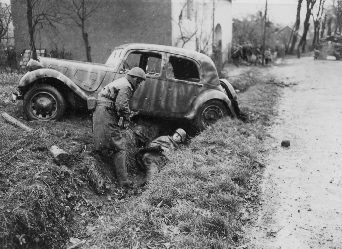 Soldiers of the 2nd Battalion de Choc, French Commandos, take cover behind a shattered German staff car during a firefight in Belfort, France on November 20, 1944.